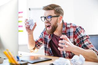 Angry crazy modern designer in glasses with beard yelling and crumpling paper on his workplace.jpeg
