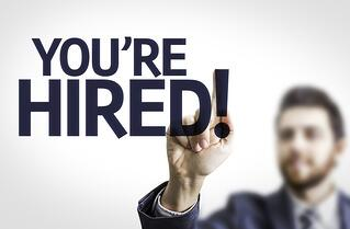 Business man pointing to transparent board with text You're Hired!.jpeg