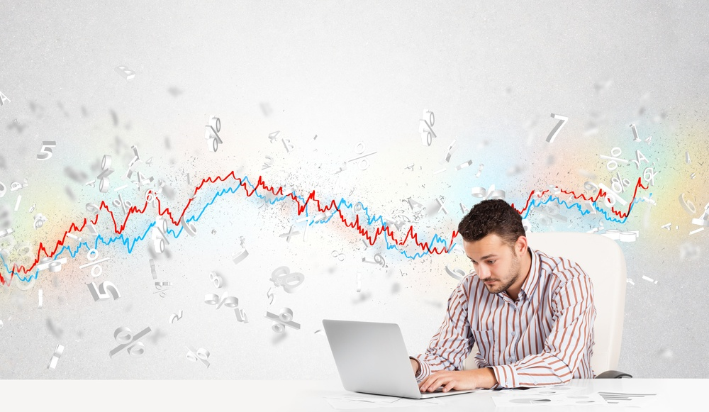 Business man sitting at table with stock market graph 3d letters.jpeg