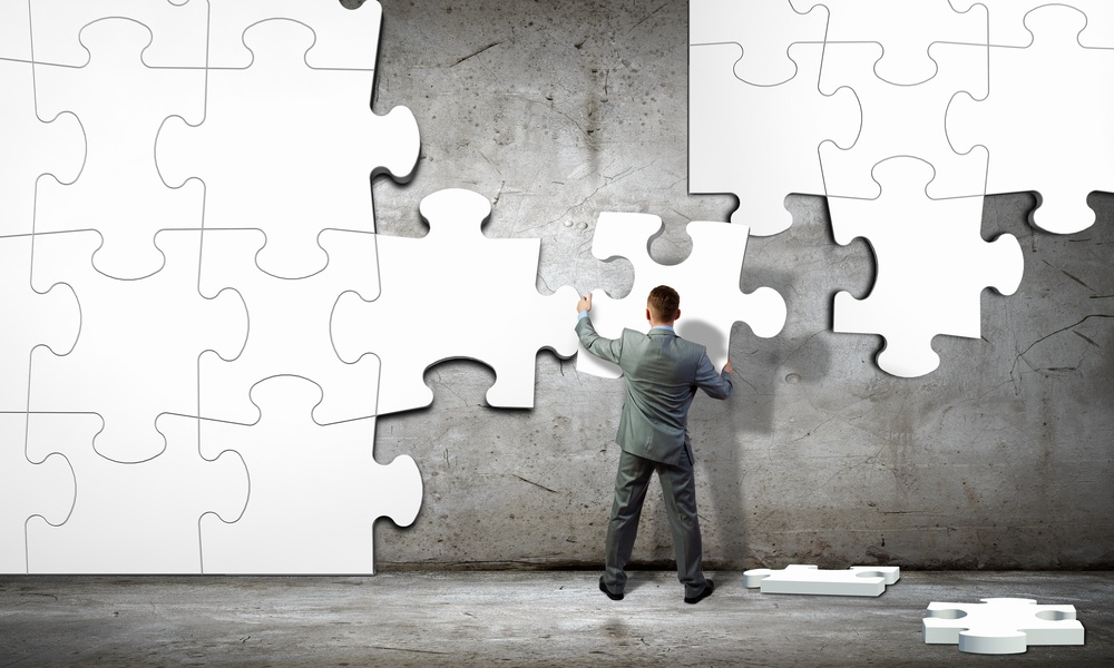 Image of businessman compiling macro white puzzle. Building business.jpeg