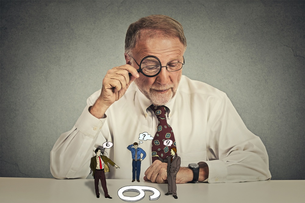 Senior business man with glasses sitting at desk skeptically looking at group arguing people through magnifying glass isolated grey wall background. Human expression, attitude. To each its own concept.jpeg