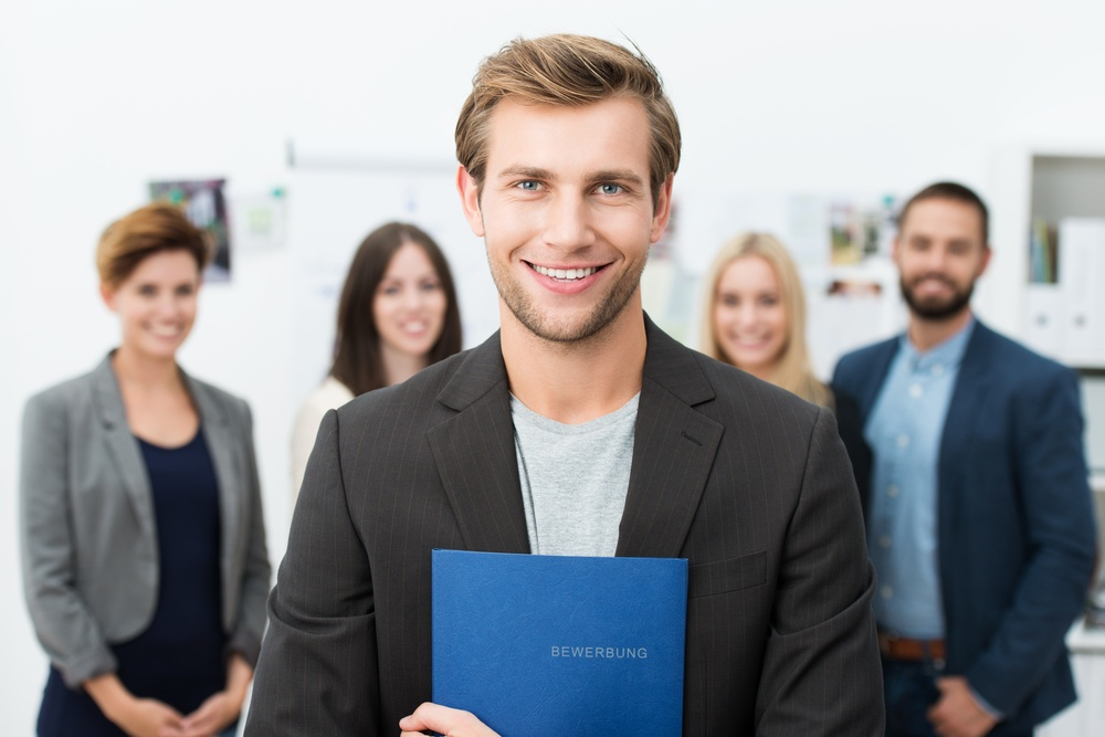 Successful smiling young male job applicant holding a blue file with his curriculum vitae posing in front of his new work colleagues or business team.jpeg