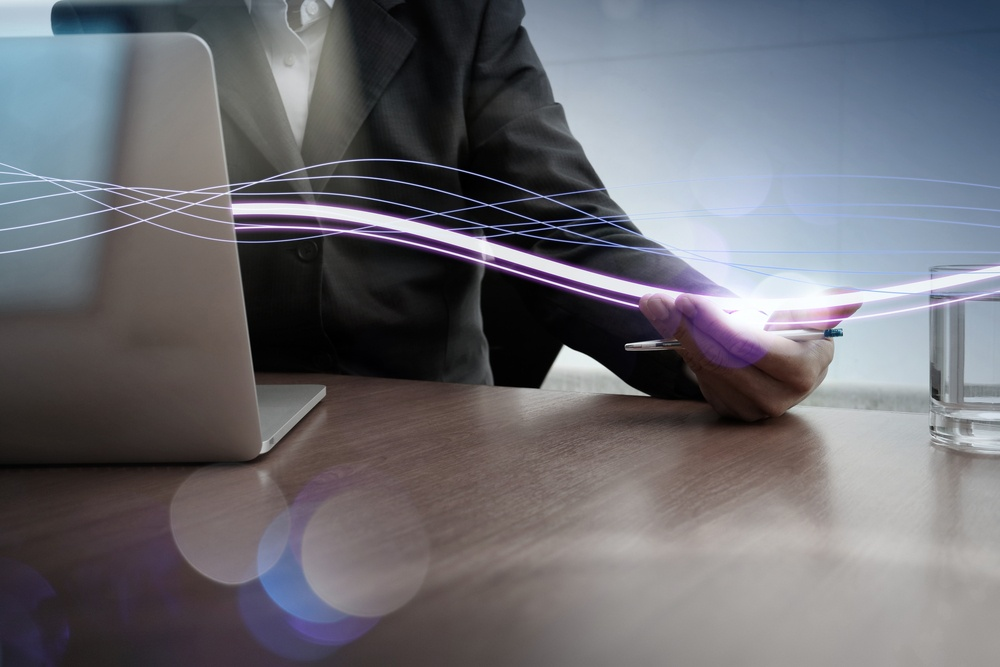 Waves of blue light and businessman using on laptop computer as concept.jpeg