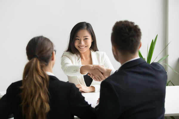 sSmiling successful young asian applicant handshake with hr manager feels happy getting hired, boss congratulating employee new job employment concept.